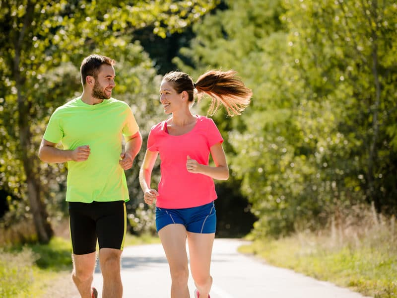 Man and woman jogging along a path in a park