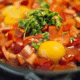 Eggs and red bell peppers in a frypan with some parsely