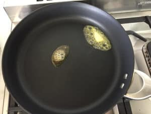 Buttersizzling in black frypan on stove