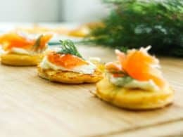 Low-Carb Smoked Salmon Blinis on a wooden board with dill in background
