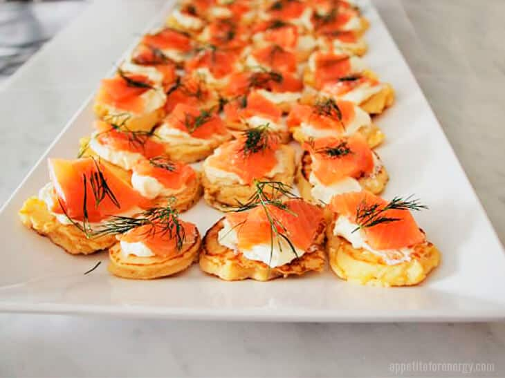Low-Carb Smoked Salmon Blinis on a long white platter for serving guests