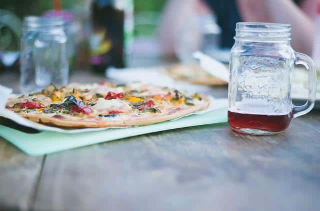 Cauliflower pizza on a table with a drink in a mason jar
