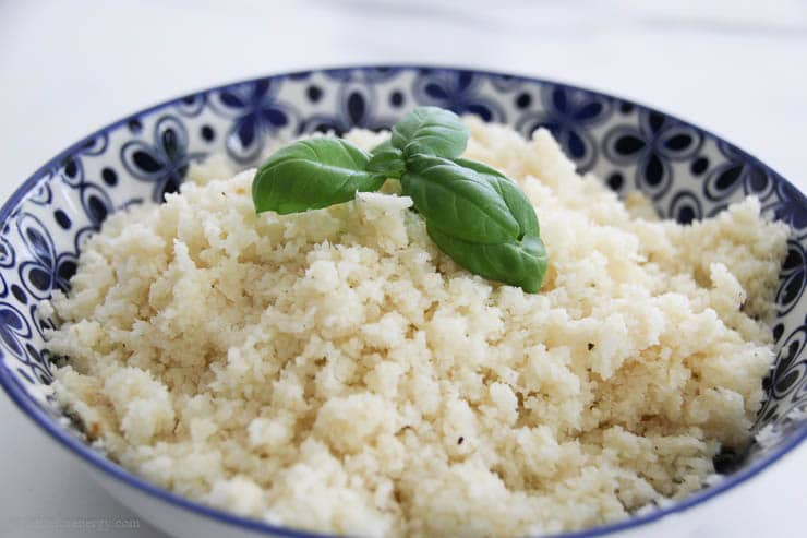 Close up of cauliflower rice in a blue bowl with basil leaves on top