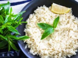 Cauliflower rice in black frypan with a wedge of lemon, a few mint leaves and a bunch of mint