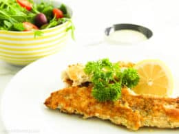 Keto Herb Crumbed Fish on a plate with Garlic Lime Aioli and a salad