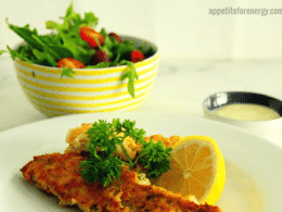 30 Minute Low Carb Herb and Parmesan Crusted Fish on a plate with lemon and a garden salad