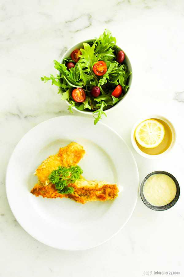 Crusted Fish With Lime Aioli in a bowl, a lemon and a side salad