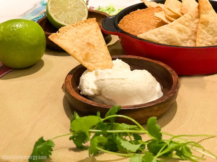 Low-Carb Tortilla Chip being dipped into bowl of sour cream, a bowl of chips, lime and cilantro