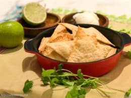 Low-Carb Tortilla Chips in a red bowl with lime, sour cream and cilantro