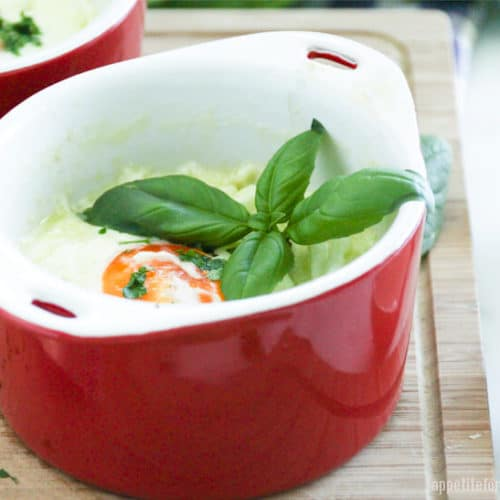 Baked eggs in a red ramekin with basil on top