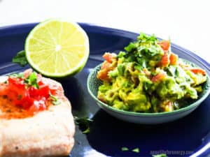 Pan Fried Salmon With Avocado Jalapeno Salsa in a bowl and half a lime
