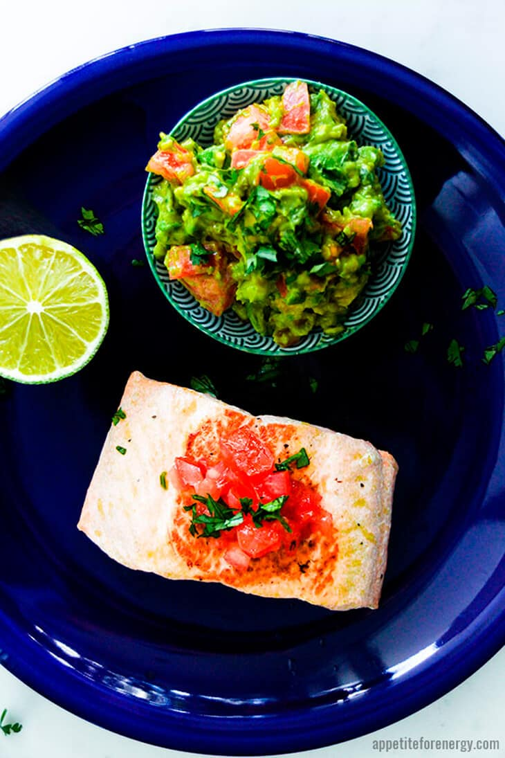 Salmon on a blue plate topped with diced tomatoes, a bowl of avovado salsa and a fresh lime