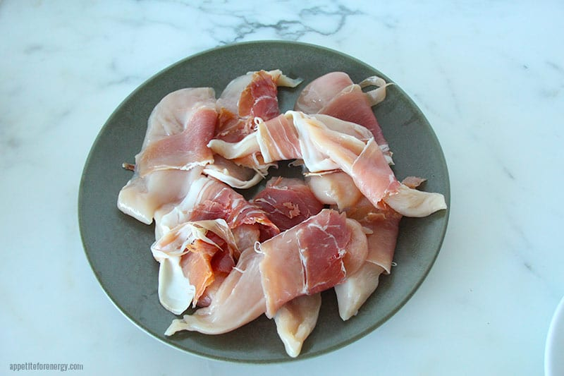 Chicken wrapped in proscuitto ready to cook, on a plate