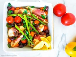 30 Minute Low-Carb Summer Chicken Tray Bake in a baking dish with tomatoes and lemons nearby
