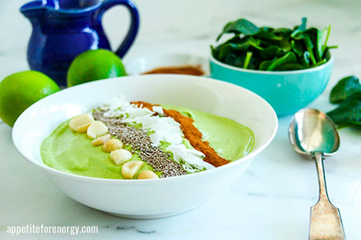 Green Keto Smoothie Bowl topped with macadamias & chia seeds with spinach, limes behind
