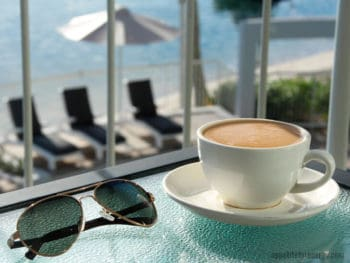 A cup of coffee on table with sunglasses and deckchairs in the background