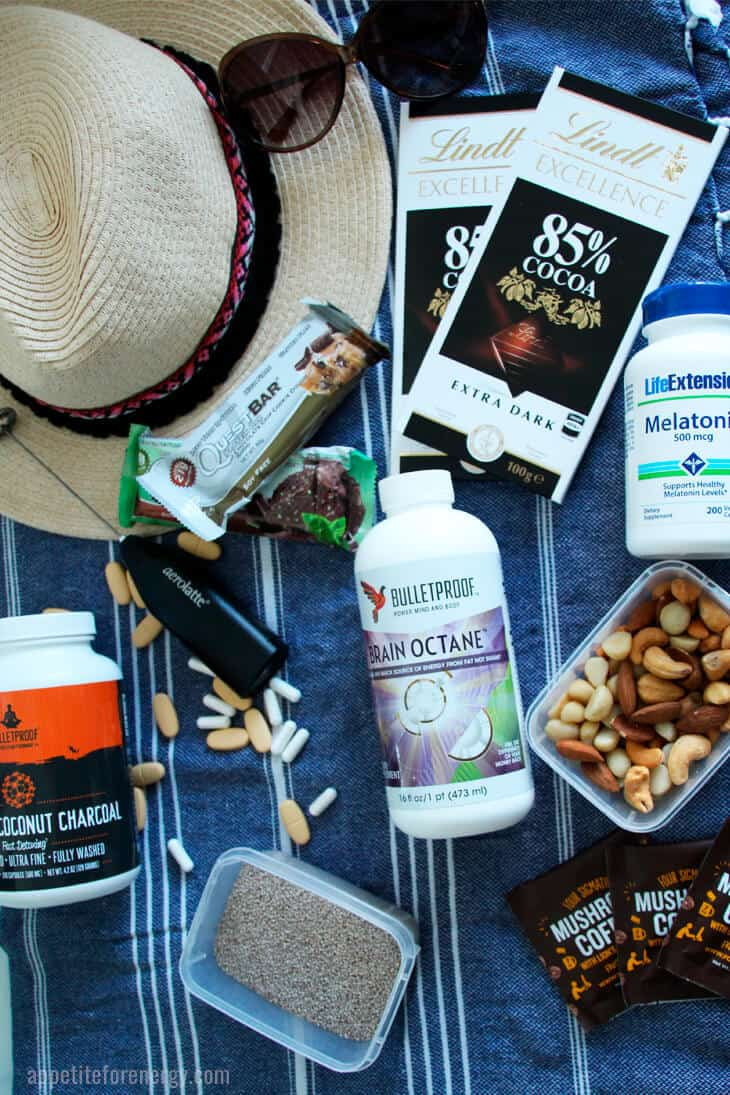 Sunhat, chocolate, nuts, supplements, aerolatte and chia seeds on a beach towel
