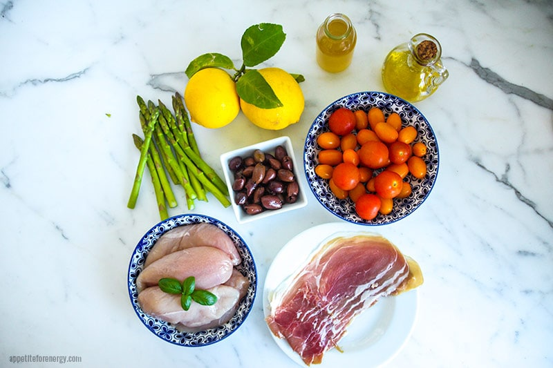 Asparagus, black olives, lemons, olive oil, cherry tomatoes, prosciutto and raw chicken in various bowls