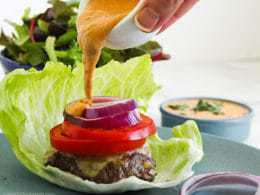 Pouring Chipotle Mayo from bowl onto a Low-Carb Burger