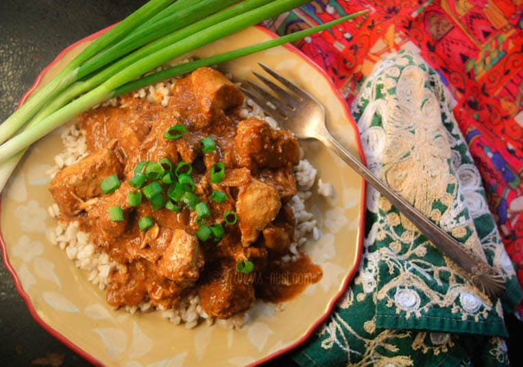 Butter chicken on a bed of cauliflower rice with spring onions on top. Served on a plate with a fork and a bright patterned tablecloth.