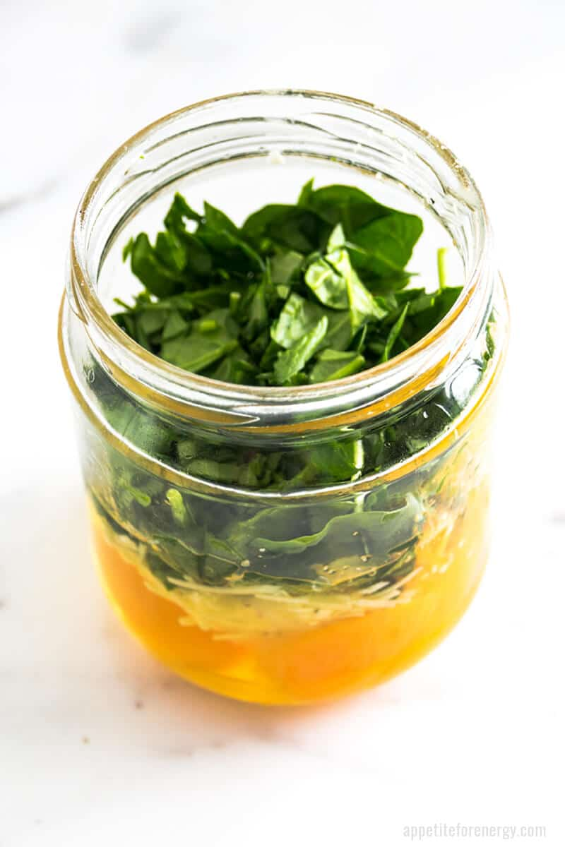 Angled view of mason jar with ingredients layered ready for cooking - raw eggs, grated cheese, spinach