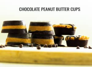 Chocolate peanut butter cups stacked up on a wooden board with choc chips scattered around