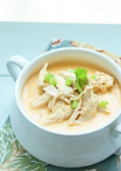 buffalo chicken soup in a bowl with herbs