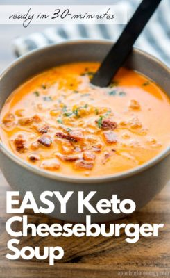 A big bowl of keto /Low Carb Cheeseburger Soup topped with bacon bits and herbs. There is a spoon in the soup.