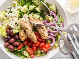 A white bowl with a bed of lettuce, black olives, halved cherry tomatoes, red onion rings, diced cucumber, crumbled feta and grilled chicken, Silver tongs lie on top of the salad