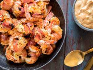 Bacon Wrapped Shrimp in a dark bowl with Remoulade Sauce in a bowl and a gold spoon