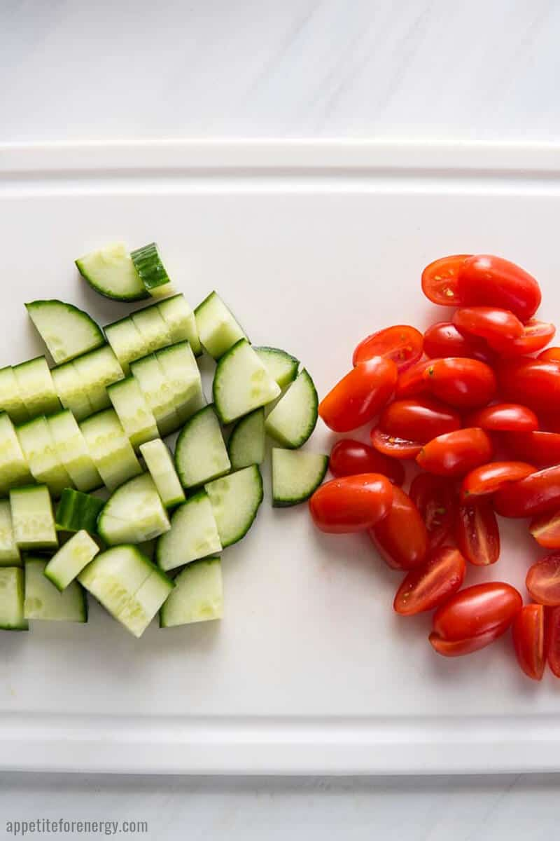 Chopped cucumbers and sliced grape tomatoes on a white cutting board