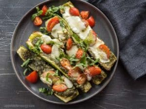 Overhead shot of four Grilled Caprese Zucchini Boats topped with tomatoes, pesto, mozzarella and basil on black plate