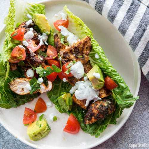 Chicken Tacos on a white plate served in a lettuce leaf and drizzled with sour cream dressing. A black and white cloth is nearby.