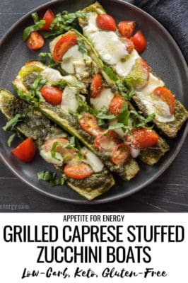 Four Grilled Caprese Zucchini Boats topped with tomatoes, pesto, mozzarella and basil