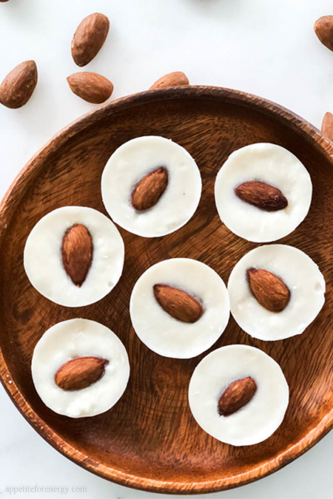 White chocolate coconut fat bombs on a wooden plate with a few scattered almonds