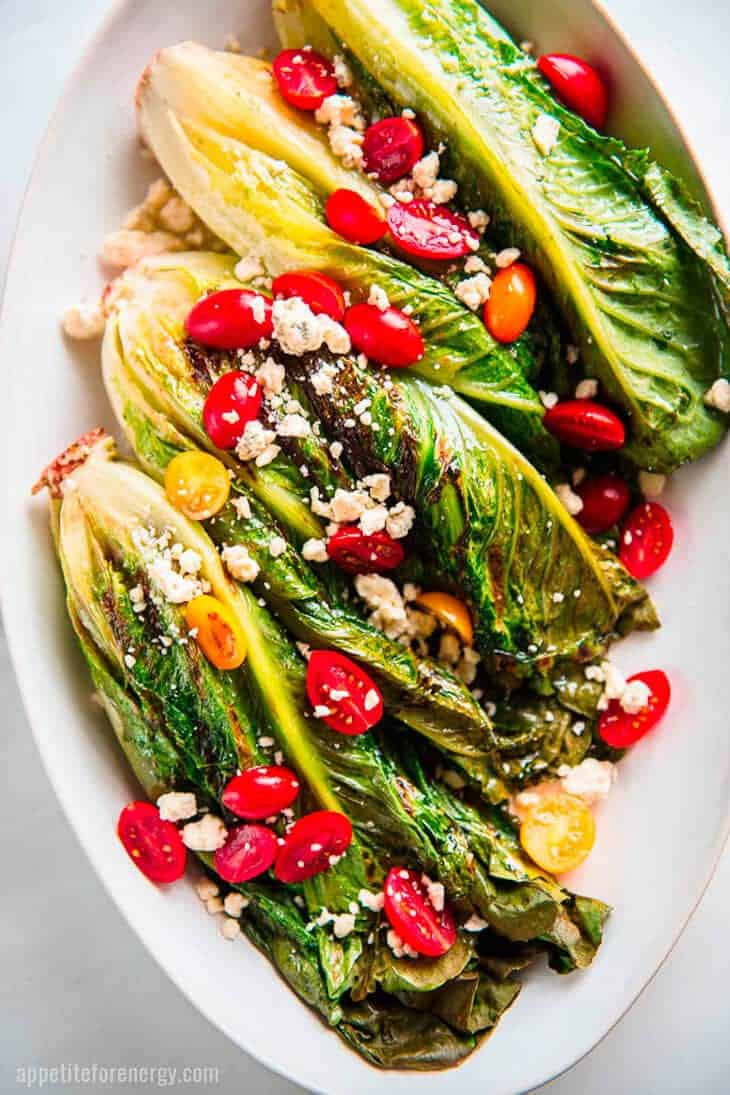 Several grilled romaine lettuces on a white platter scattered with grape tomatoes and blue cheese