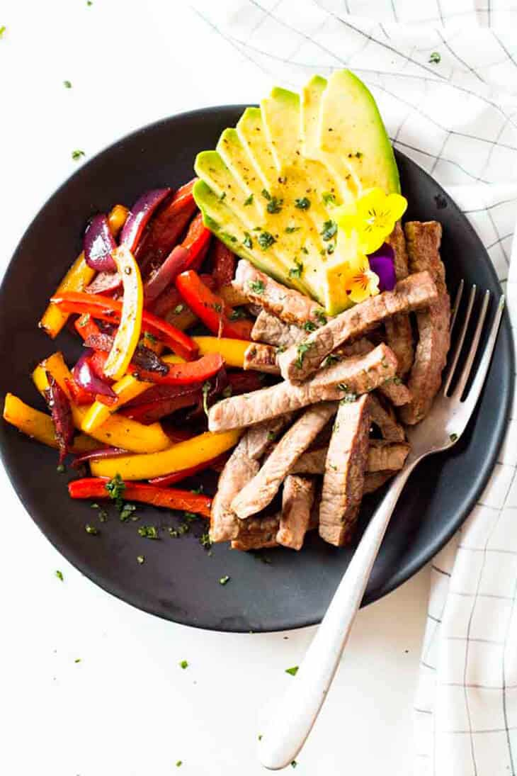 Beef fajitas with red onion, bell peppers and avocado in a black bowl with fork