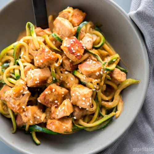 Crispy Pork LO Mein with Zoodles in a light grey bowl with a grey napkin and black spoon