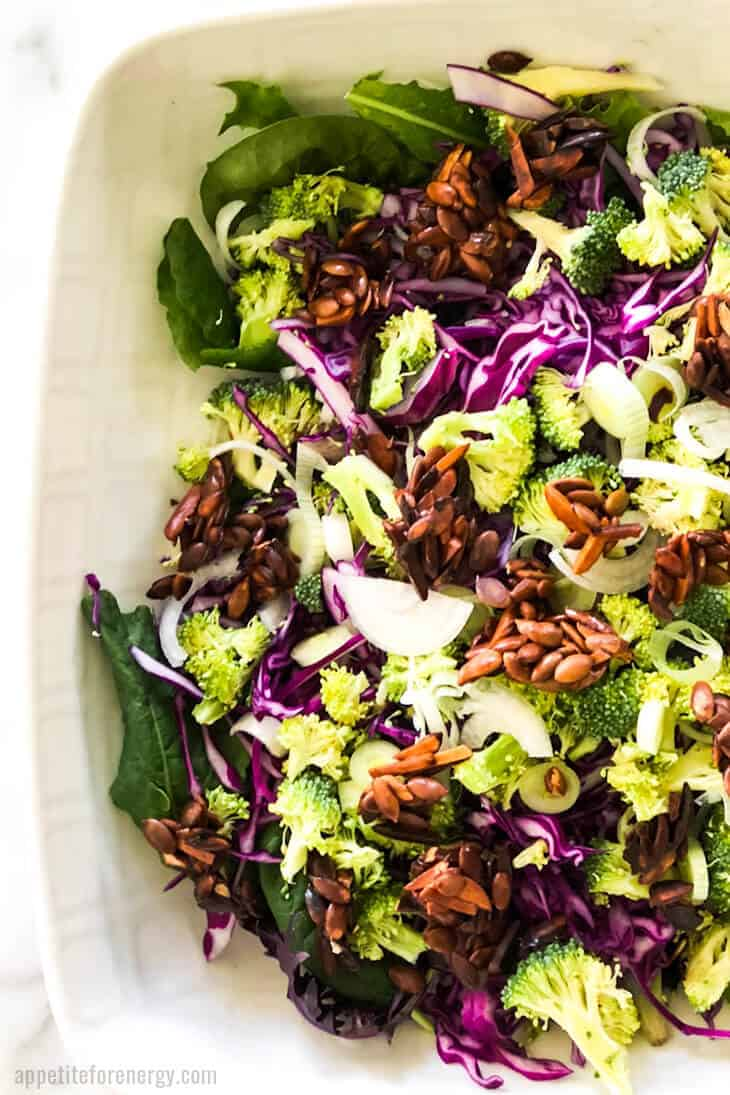 Crunchy Broccoli Slaw in a white serving bowl, topped with nut clusters