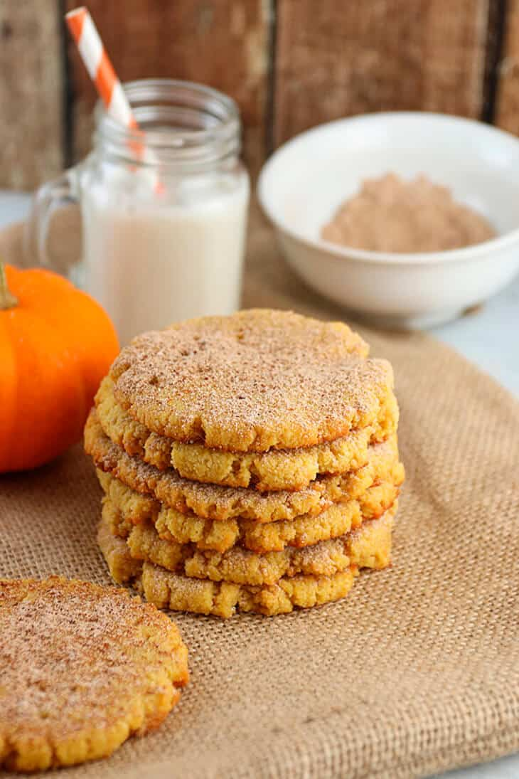 A stack of Keto Pumpkin Snickerdoodle Cookies in front of a small pumpkin, glass of milk and bowl of spice