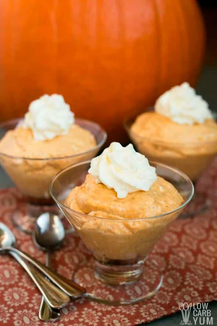 3 servings of Low-Carb Pumpkin Mousse in glass bowls, topped with whipped cream. A giant pumpkin in background