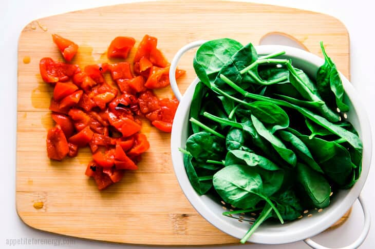 Chopped marinated peppers and spinach in a colander, both on a wooden board