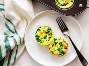 Overhead shot of 2 Spinach and Red Pepper Egg Bites on a plate with a fork and more egg bites in the muffin tin