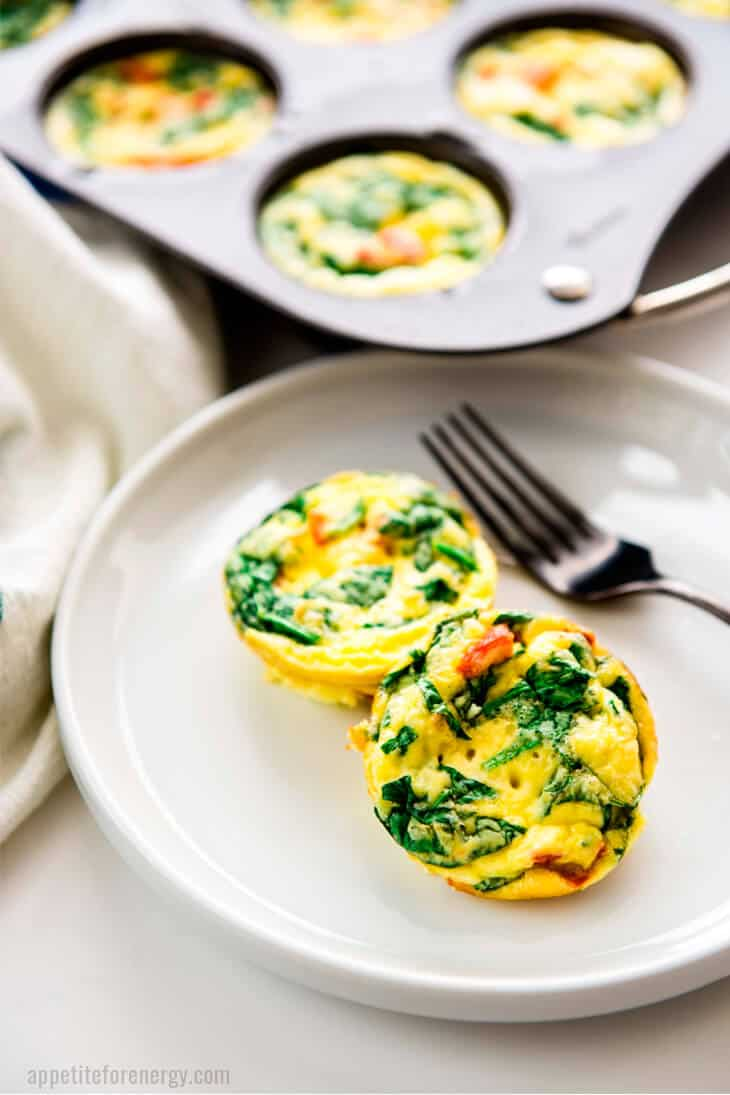 2 Spinach and Red Pepper Egg Bites on a plate with a fork and more egg bites in the muffin tin