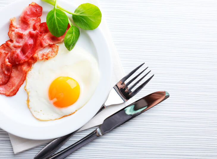 Bacon and eggs on a white plate with a knife and fork, napkin