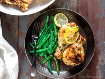 Overhead shot of Chicken Drumsticks on a black plate with green beans