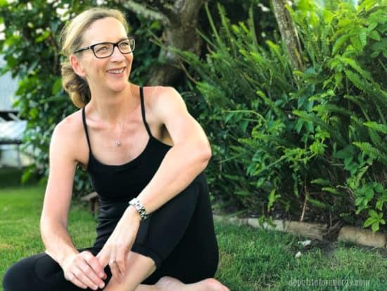 Anna Mazlin sitting on a lawn cross legged, laughing