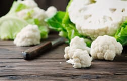 Cauliflower florets on a wooden chopping board with sharp knife ready to be cooked