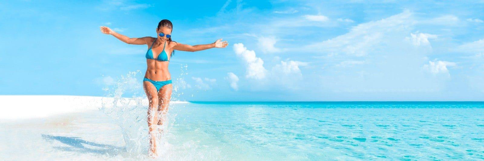 Happy Girl splashing in water on beach