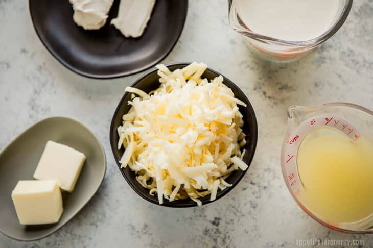 Grated cheese, cream cheese, cream, broth and butter in bowls